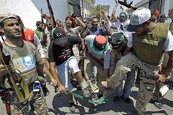 Rebellenkämpfer zerreißen eine grüne Flagge, das Symbol für die Ära Gaddafi.
