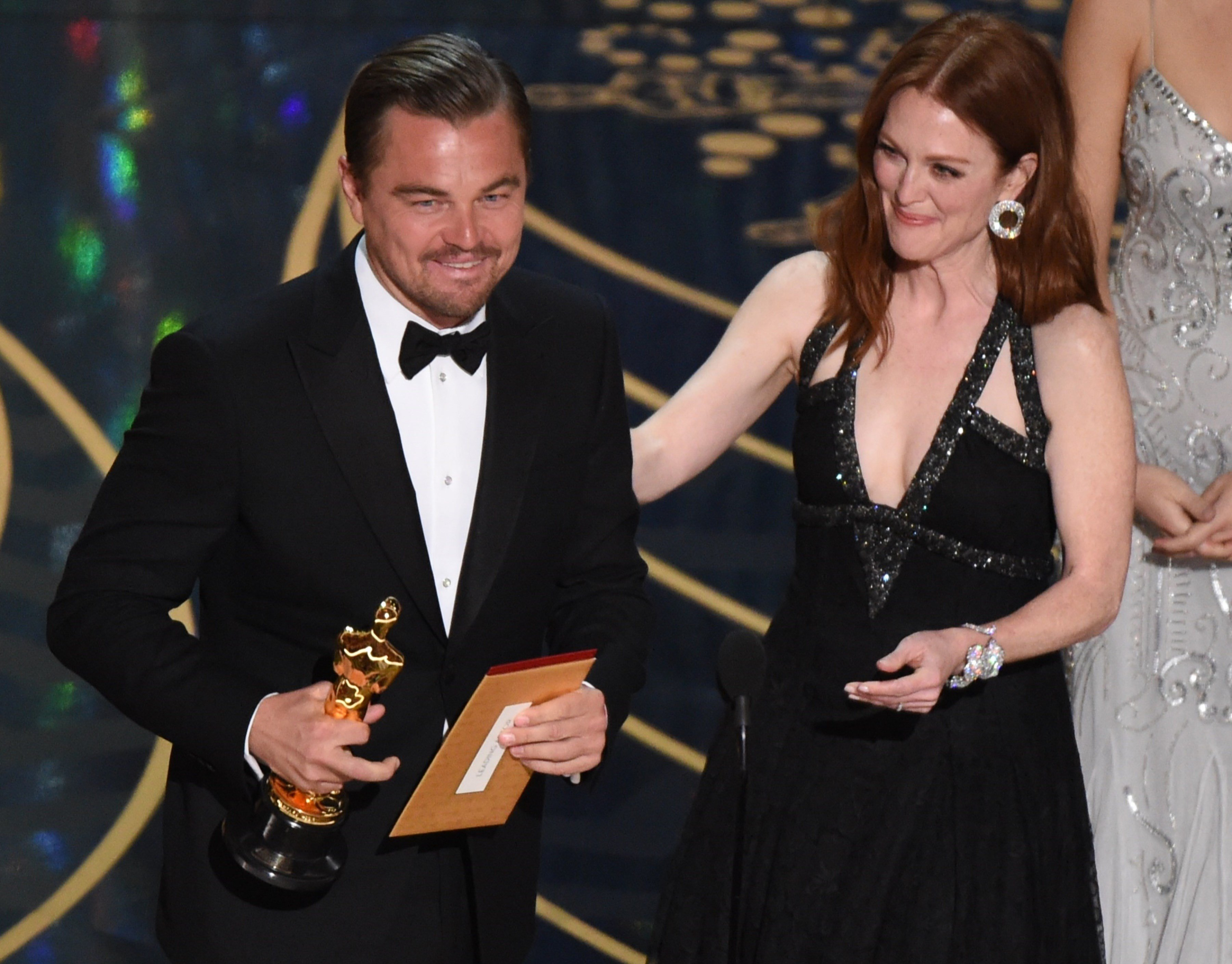 Actor Leonardo DiCaprio accepts the award for Best Actor in,The Revenant from actress Julianne Moore on stage at the 88th Oscars on February 28, 2016 in Hollywood, California. AFP PHOTO / MARK RALSTON