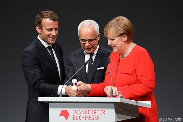 Macron und Merkel mit Börsenverein-Boss Riethmüller